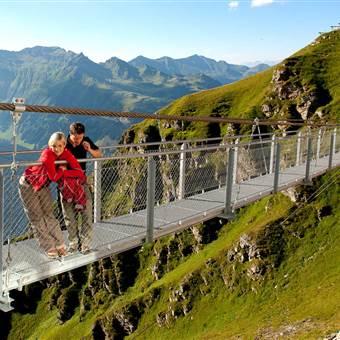 Paar steht auf einer Hängebrücke in den Bergen
