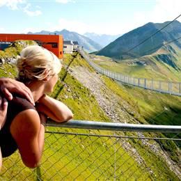 Menschen auf Hängebrücke in den Bergen im Sommer