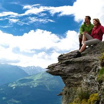 Paar sitzt auf einem Felsen in den Bergen