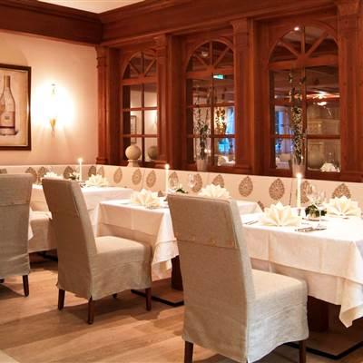 Restaurantbereich mit gedeckten Tischen bei Kerzenschein und Weinflaschen