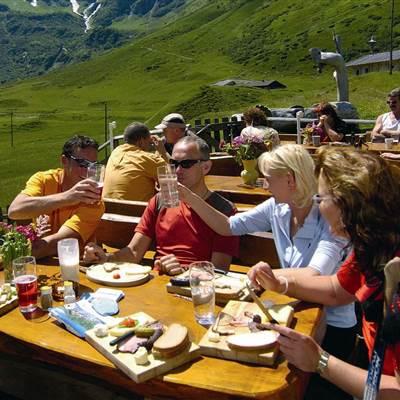 Wandergruppe trinkt und isst auf einer Wanderhütte in den Bergen
