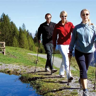 Wandergruppe geht von Wanderhütte Richtung Bergsee