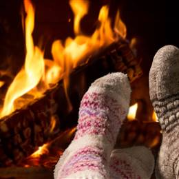 Feet in wool socks in front of the fireplace in detail