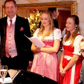 Familie singt in festlicher Kleidung und wird am Klavier begleitet
