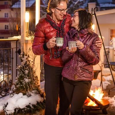 Paar trinkt Heißgetränk auf einer Hotelterrasse im Winter