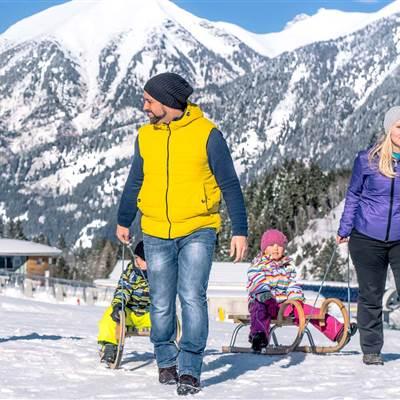 Familie mit Schlitten in Winterlandschaft