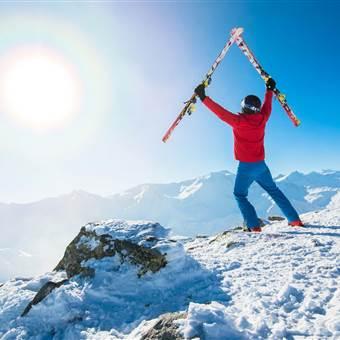 Skifahrer hält Skier in die Luft auf einem Berg