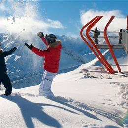 Paar in Skioutfit im Schnee bei strahlendem Sonnenschein