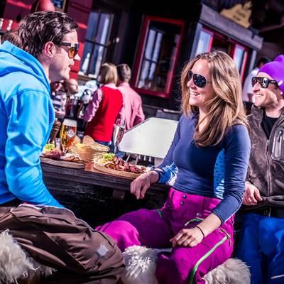 Freunde beim Apres Ski auf eine Skihütte in den Bergen