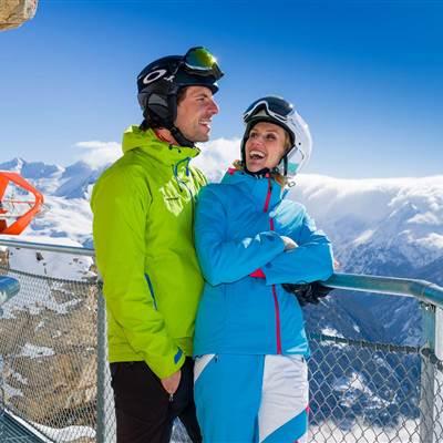 Paar in Skibekleidung steht auf einer Aussichtsplattform in den Bergen