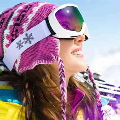 Skifahrerin mit Skibrille bei Sonnenschein im Close-Up