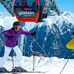 Skiers on the ski slope in front of gondola and mountain landscape