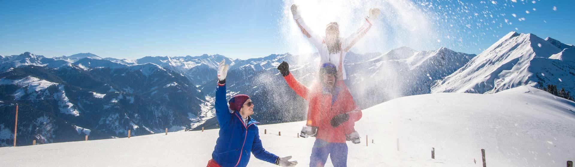 Freunde stehen vor Berglandschaft im Winter und werfen Schnee in die Luft