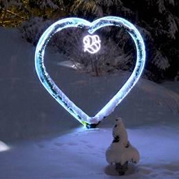 Illuminated heart in winter landscape at night