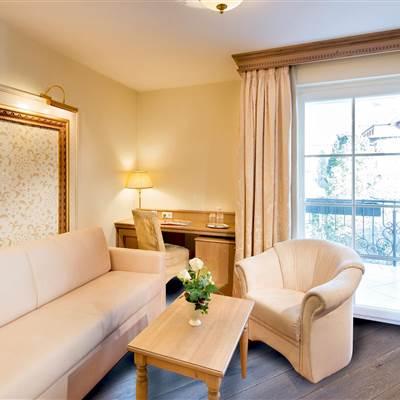 Hotelzimmer mit Sofa, Schreibtisch, Tisch, Stuhl und Balkonzugang